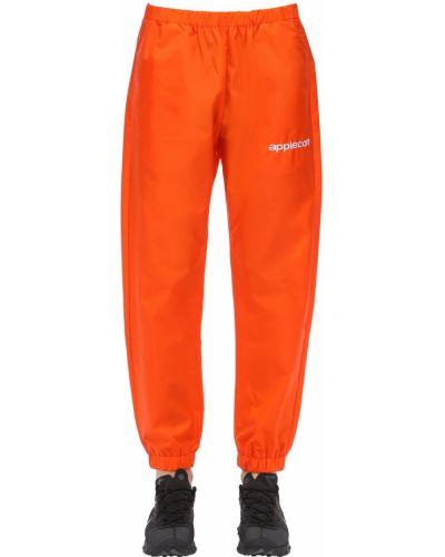 Pomarańczowe spodnie z printem Applecore