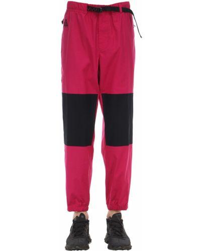 Różowe spodnie bawełniane z paskiem Nike Acg