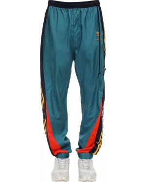 Zielone spodnie w paski Adidas Originals Statement