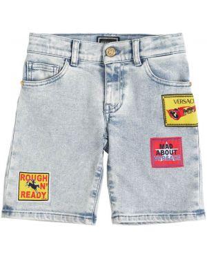 Jeansy na gumce z łatami Versace